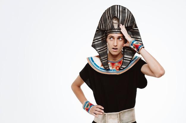 Mężczyzna w starożytnym egipskim stroju patrzący na bok zdezorientowany, trzymający rękę na głowie na białym tle