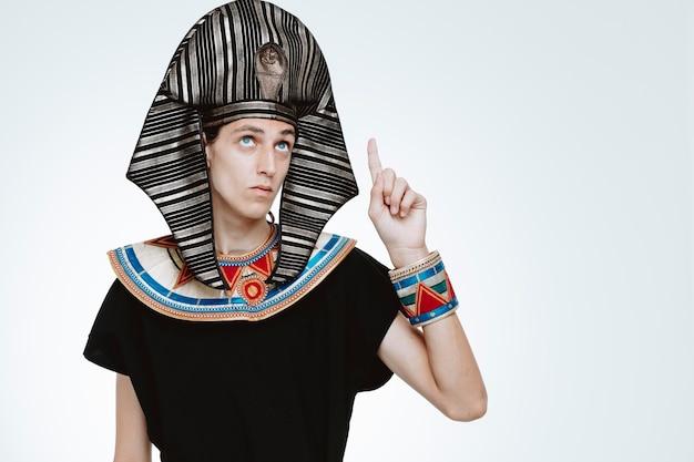Mężczyzna w starożytnym egipskim stroju patrzący w górę z poważną twarzą wskazującą palcem wskazującym na biały