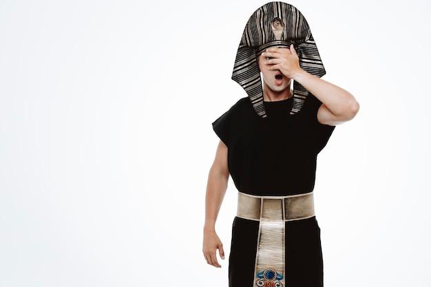 Mężczyzna w starożytnym egipskim stroju przez dłoń przestraszony na biało