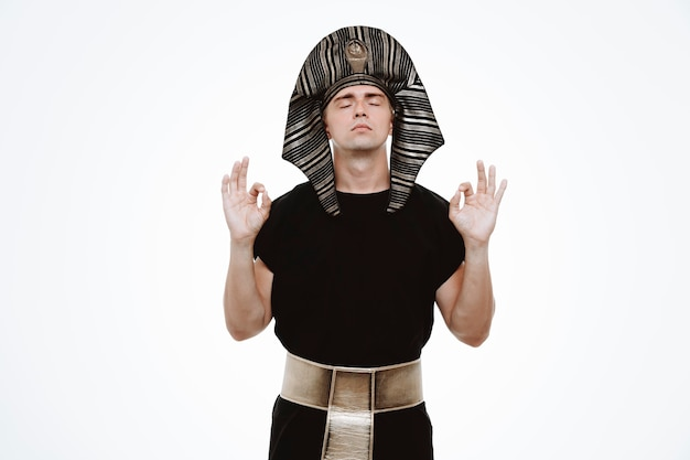 Mężczyzna w starożytnym egipskim stroju relaksuje się wykonując gest medytacyjny palcami na białym