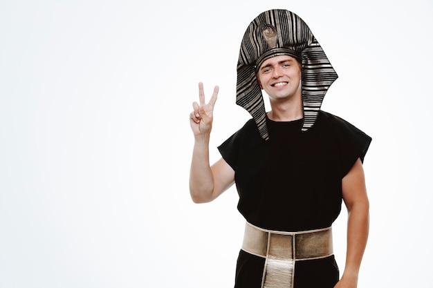 Mężczyzna w starożytnym egipskim stroju szczęśliwy i pozytywny pokazując znak v lub numer dwa na białym