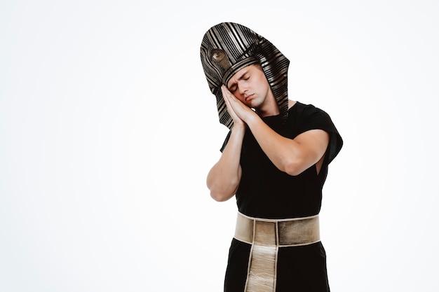 Mężczyzna w starożytnym egipskim stroju, trzymający dłonie razem, opierając głowę na dłoniach, chce spać na biało