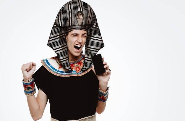 Mężczyzna w starożytnym egipskim stroju trzymający smartfona zaciskający pięści podekscytowany i szalony szczęśliwy cieszący się swoim sukcesem na białym tle