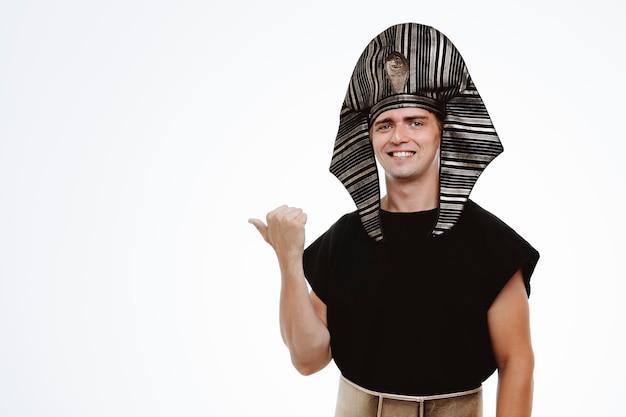 Mężczyzna w starożytnym egipskim stroju uśmiechający się pewnie, wskazując kciukiem na bok na białym tle