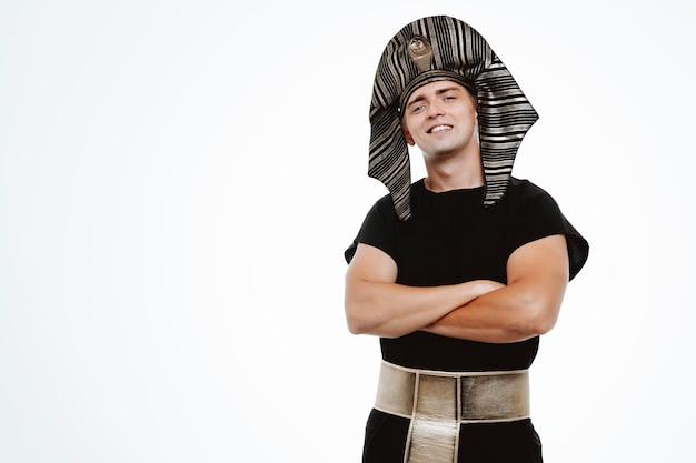 Mężczyzna w starożytnym egipskim stroju z pewnym siebie uśmiechem na twarzy ze skrzyżowanymi rękami na piersi na białym tle