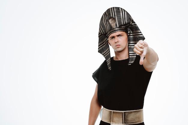 Mężczyzna w starożytnym egipskim stroju z poważną twarzą pokazującą kciuk w dół na białym tle