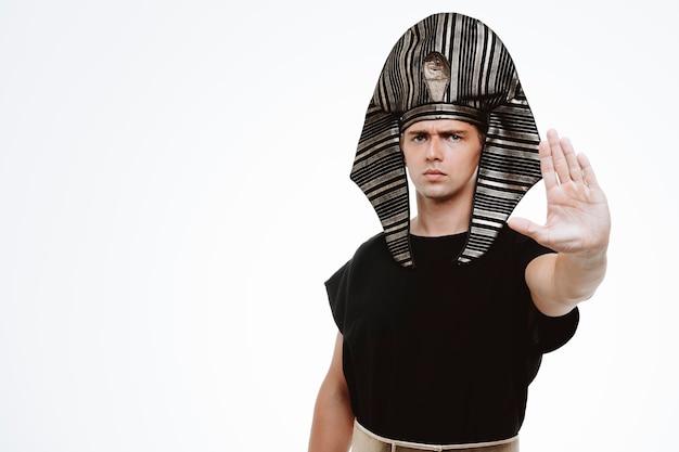 Mężczyzna w starożytnym egipskim stroju z poważną twarzą wykonującą gest zatrzymania ręką na białym
