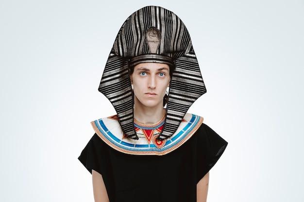 Mężczyzna w starożytnym egipskim stroju z poważnym, pewnym siebie wyrazem twarzy na białym