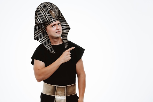 Mężczyzna w starożytnym egipskim stroju z uśmiechem na twarzy wskazującym palcem wskazującym na bok na białym tle