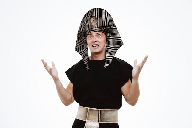 Mężczyzna w starożytnym egipskim stroju zdezorientowany i podekscytowany, podnoszący ręce na białym tle