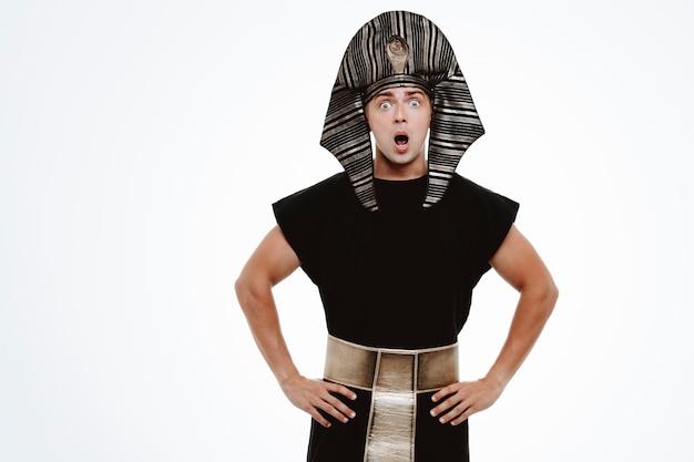 Mężczyzna w starożytnym egipskim stroju zdumiony i zaskoczony na białym tle