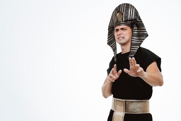 Mężczyzna w starożytnym egipskim stroju zmartwiony i przestraszony wykonujący gest obronny rękami na białym