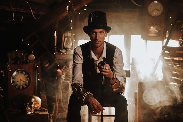Mężczyzna w steampunkowym garniturze z kapeluszem, cylindrem i laską w bajecznym warsztacie zegarmistrzowskim