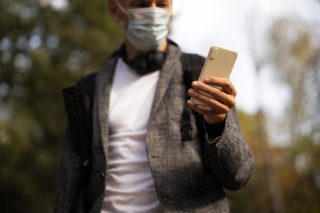Mężczyzna w sterylnej masce używający smartfona na zewnątrz