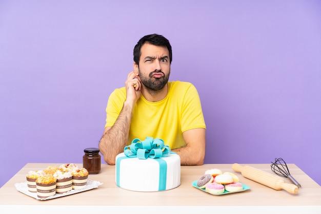 Mężczyzna w stole z dużym ciastem mającym wątpliwości