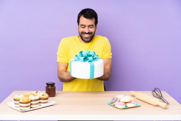 Mężczyzna w stole z dużym ciastem na fioletowo