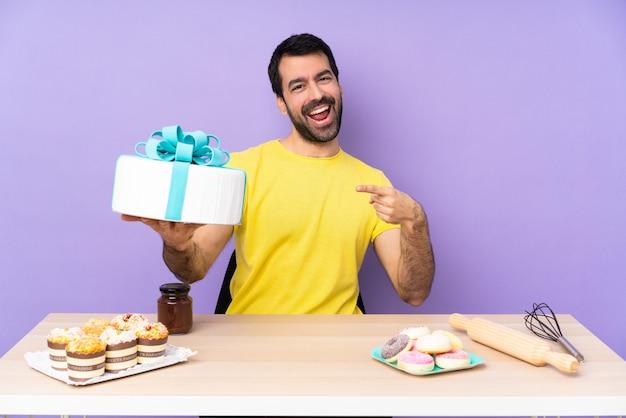 Mężczyzna w stole z dużym ciastem na ścianie fioletowy