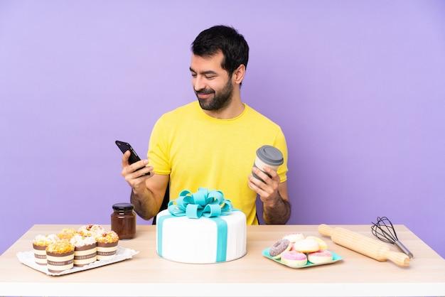 Mężczyzna w stole z dużym ciastem, trzymając kawę na wynos i telefon komórkowy