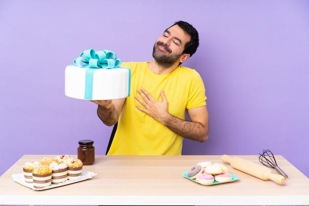 Mężczyzna w stole z dużym tortem na purpurowym backgroun