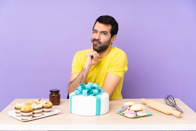 Mężczyzna w stole z dużym tortem nad odosobnioną purpury ścianą
