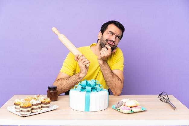 Mężczyzna w stole z dużym tortem nad purpurowym deseniem