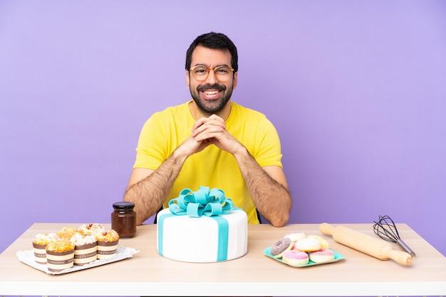 Mężczyzna w stole z dużym tortem w okularach i uśmiechnięty