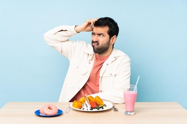Mężczyzna w stole z goframi nad odosobnioną błękit ścianą
