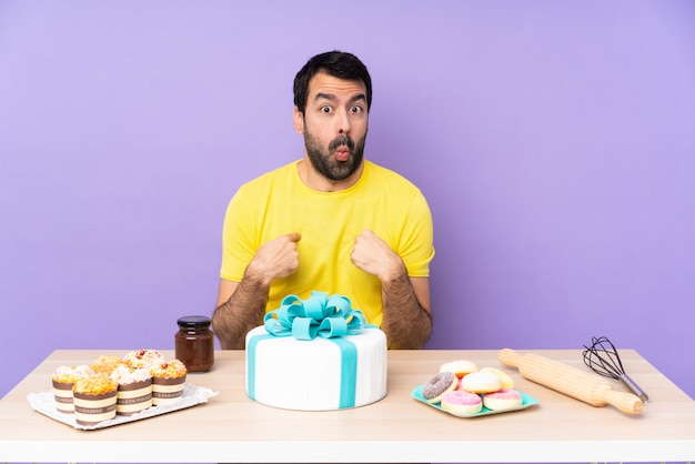 Mężczyzna w stole z wielkim tortem skierowanym do siebie