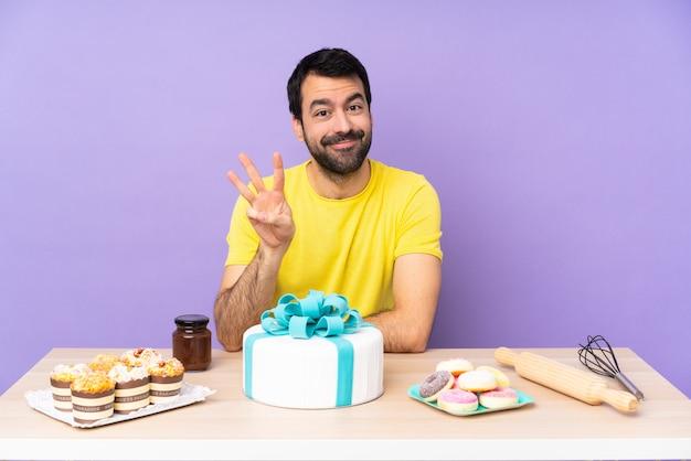 Mężczyzna w stole z wielkim tortem szczęśliwy i licząc trzy z palcami