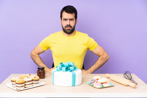 Mężczyzna w stole z wielkim tortem zły