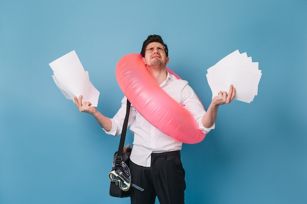 Mężczyzna w stroju biurowym płacze, trzymając dużo kartek papieru. facet chce pojechać na wakacje i pozować z nadmuchiwanym kółkiem na niebieskiej przestrzeni.