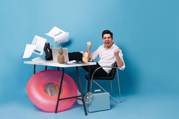 Mężczyzna w stroju biurowym raduje się podczas pracy na laptopie wśród spadających arkuszy papieru. facet w okularach pozuje z ananasem, walizką i maską do nurkowania.