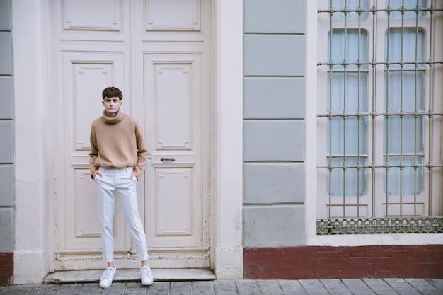 Mężczyzna w stroju casual stojący przy drzwiach wejściowych