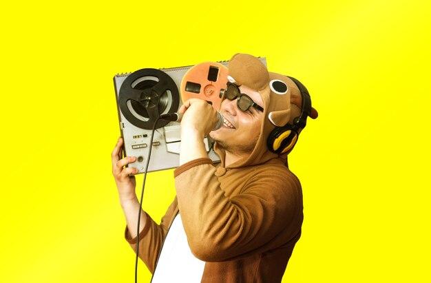 Mężczyzna w stroju cosplay krowa śpiewa karaoke. facet w piżamie zwierzęcej trzyma mikrofon. śmieszne zdjęcie z magnetofonem szpulowym. pomysły na imprezy. dyskotekowa muzyka retro.