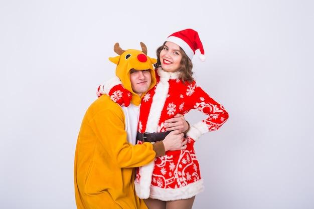 Mężczyzna w stroju jelenia i kobieta w stroju świętego mikołaja w pobliżu choinki