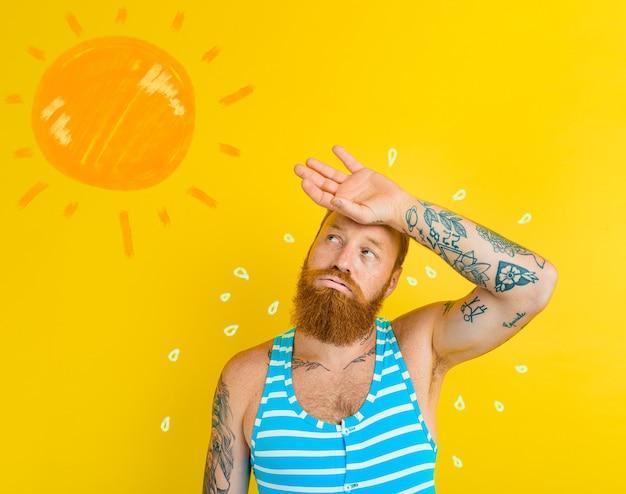 Mężczyzna w stroju kąpielowym poci się z powodu zbyt gorącego słońca