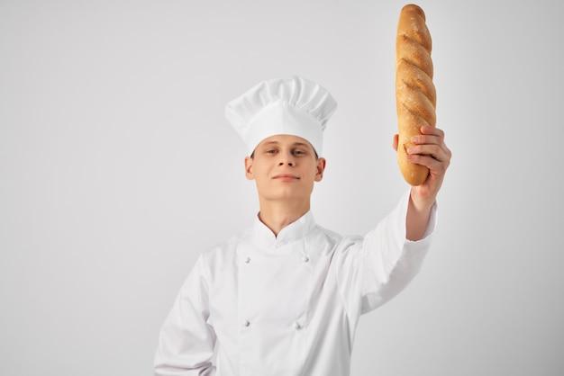 Mężczyzna w stroju kucharza z bochenkiem w rękach wykwintnego piekarza pracy