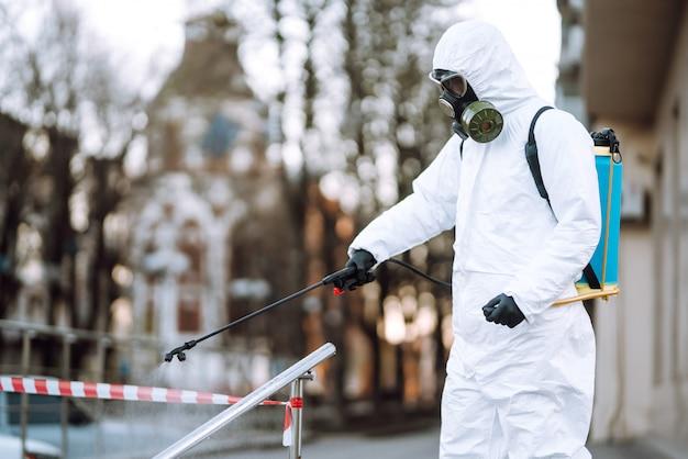 Mężczyzna w stroju ochronnym i masce rozpyla dezynfektor na poręcz w pustym miejscu publicznym o świcie w mieście kwarantanny. covid 19. koncepcja czyszczenia.