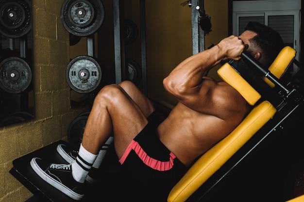 Mężczyzna w stroju sportowym budujący nogi za pomocą urządzenia gimnastycznego