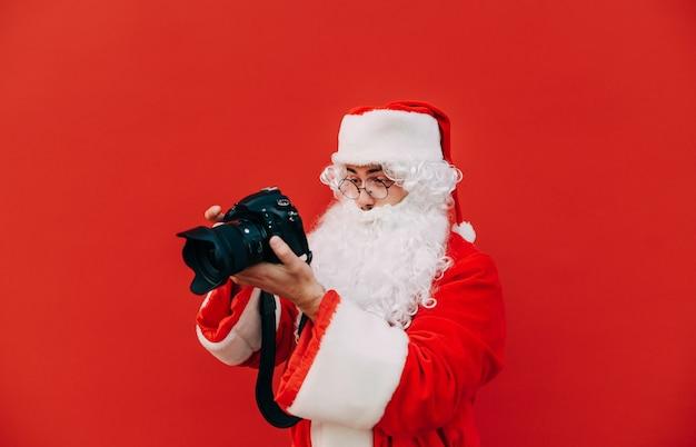 Mężczyzna w stroju świętego mikołaja czuje zainteresowanie i fascynację aparatem fotograficznym