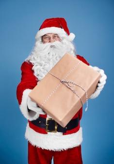 Mężczyzna w stroju świętego mikołaja daje prezenty świąteczne