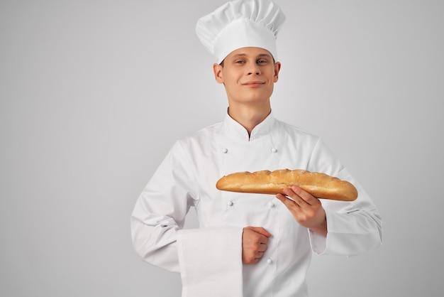 Mężczyzna w stroju szefa kuchni patrzący na bochenek profesjonalnej branży piekarniczej