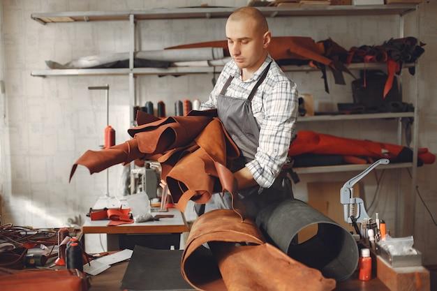 Mężczyzna w studio tworzy galanterię skórzaną