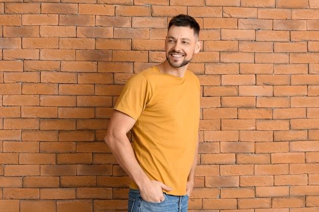 Mężczyzna w stylowej koszulce w pobliżu ceglanego muru