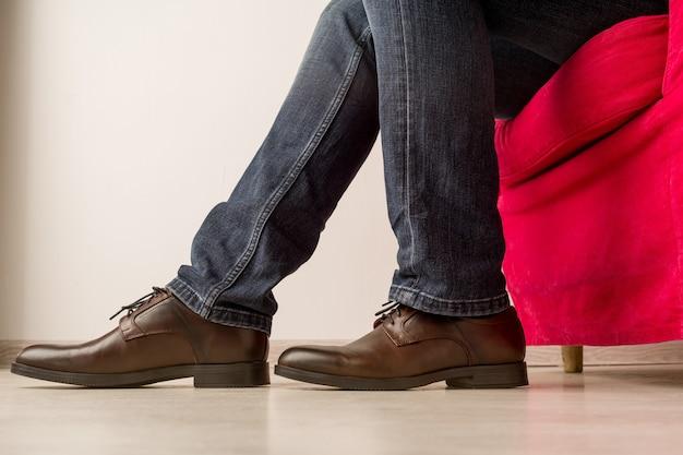 Mężczyzna w stylowych brązowych butach siedzi na czerwonym fotelu