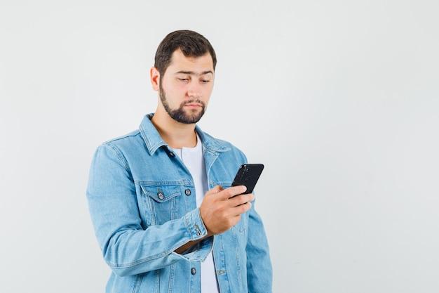 Mężczyzna w stylu retro czyta coś na telefon komórkowy w kurtce, t-shirt i patrząc skoncentrowany, widok z przodu.