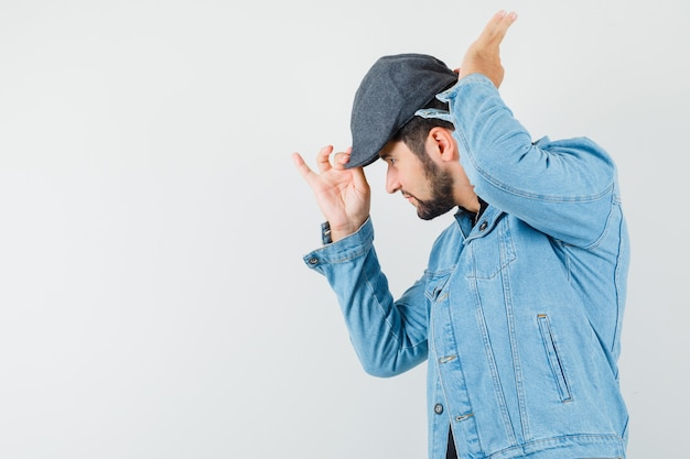 Mężczyzna w stylu retro, dostosowując czapkę w kurtkę, czapkę i patrząc skoncentrowany, widok z przodu. miejsce na tekst