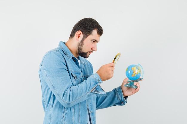 Mężczyzna w stylu retro patrząc na mini kulę ziemską z lupą w kurtce, t-shirt i patrząc skupiony. .