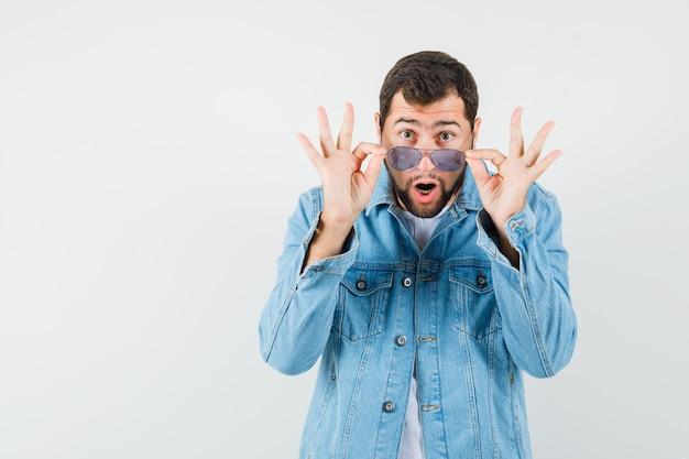 Mężczyzna w stylu retro, patrząc na okulary w kurtce, t-shirt i wyglądający dziwnie, widok z przodu.