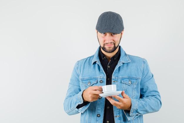 Mężczyzna w stylu retro trzyma kubek w kurtce, czapce, koszuli i wygląda na zadowolonego, widok z przodu.